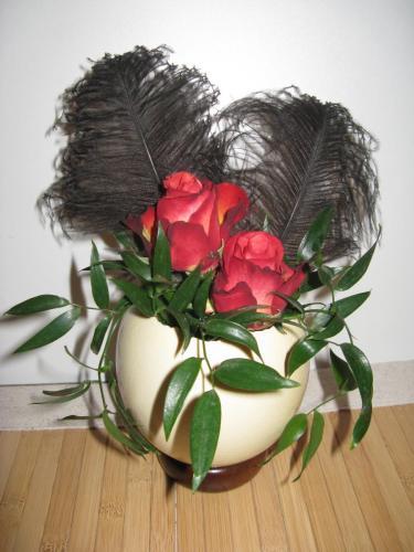 Vase mit Rosen und Federn
